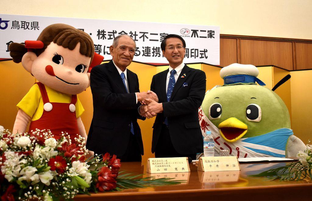 連携協定締結後、握手を交わす鳥取県の平井伸治知事(右)と不二家の山田憲典会長=鳥取市