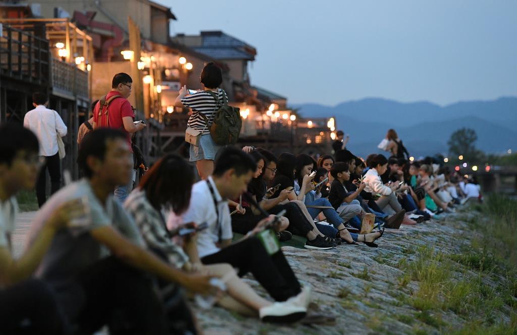 夕暮れどき、河川敷に座ってくつろぐ人たち