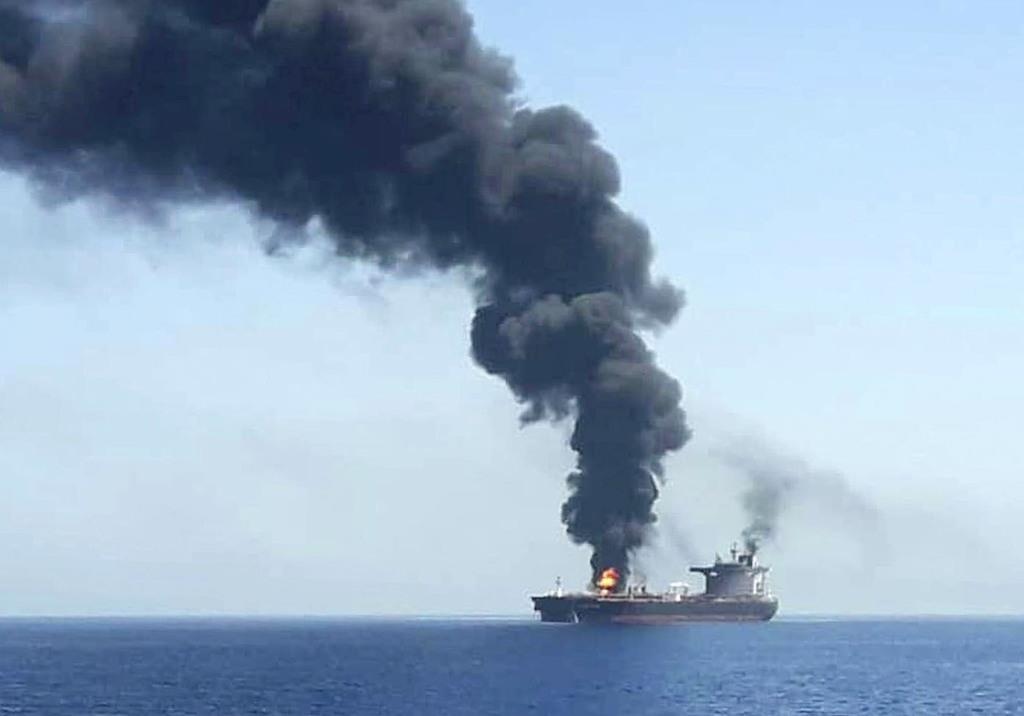 13日、ホルムズ海峡付近で攻撃を受け、オマーン湾で煙を上げるタンカー。2隻が攻撃を受けたが、いずれのタンカーかは不明(国営イラン放送提供・AP=共同)