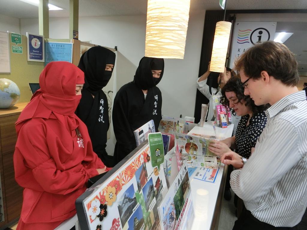 京都からの訪日客を呼び込もうと忍者姿で滋賀の観光情報を紹介するスタッフ=13日、京都市