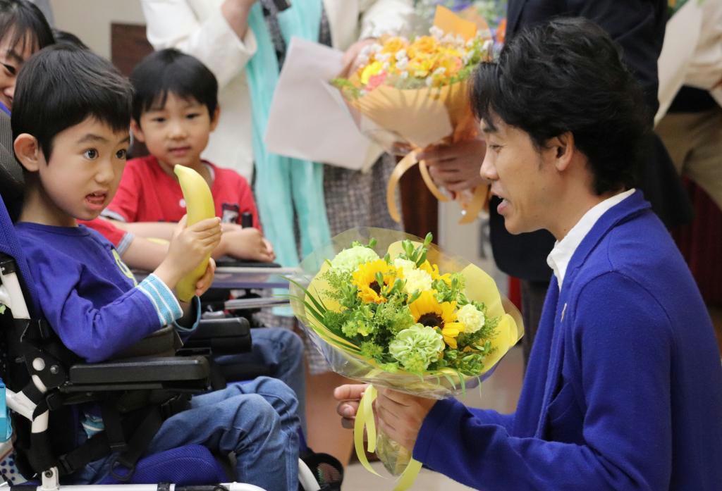 日本筋ジストロフィー協会全国大会のトークショーで、バナナを持つ患者の男児から花束を受け取る大泉洋さん(右)=5月19日、東京都内 (日本筋ジストロフィー協会提供)