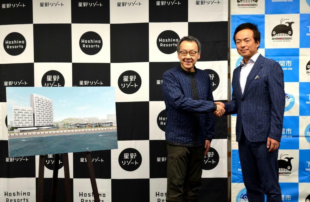 ホテルの完成予想図の側で握手する星野佳路氏(左)と前田晋太郎・下関市長