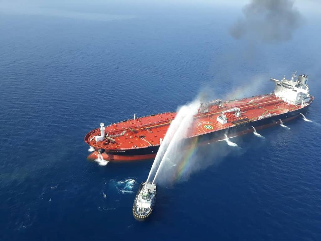 タンカーの消火を行うイラン海軍のボート=13日、オマーン湾(ロイター)
