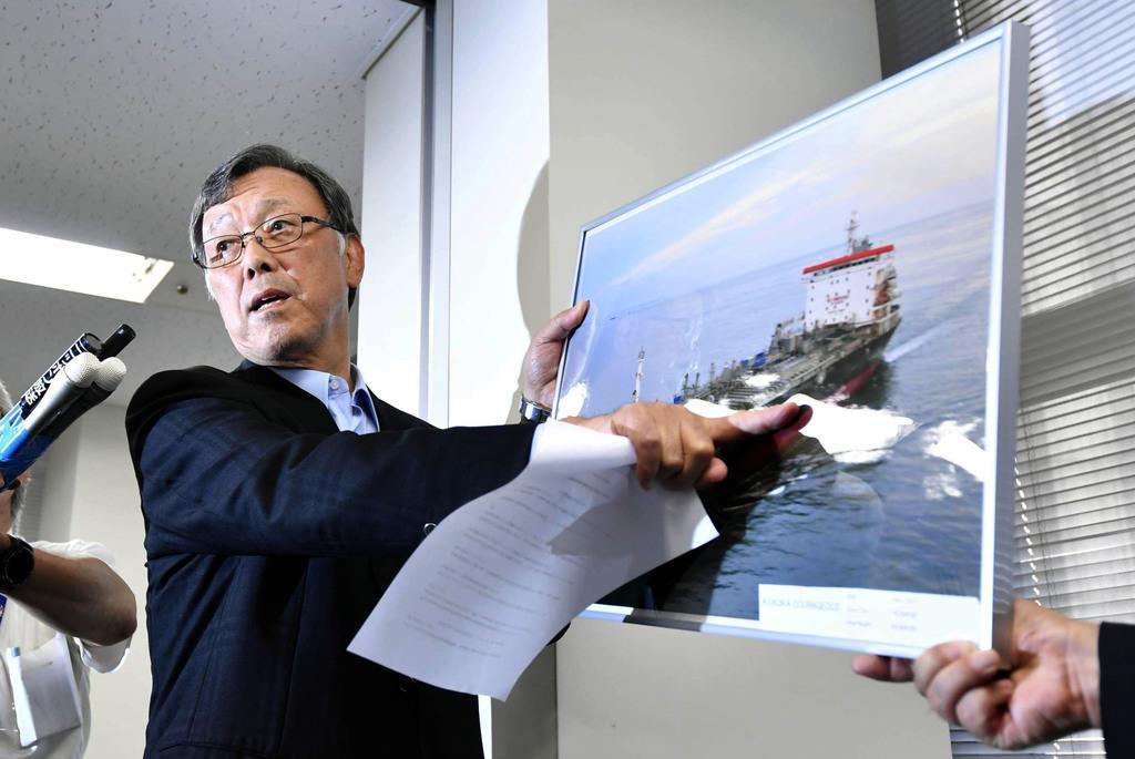 記者会見で、タンカーの写真を指さし説明する国華産業の堅田豊社長=14日午後、東京都千代田区