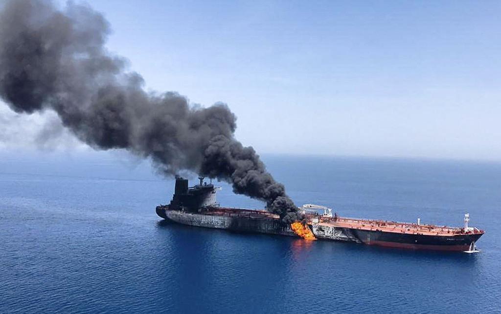 13日、ホルムズ海峡付近で攻撃を受けて火災を起こし、オマーン湾で煙を上げる日本のタンカー(AP)
