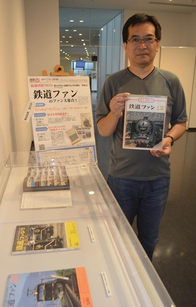 創刊200号を手にする岡田隆義さん=兵庫県伊丹市の市立図書館本館