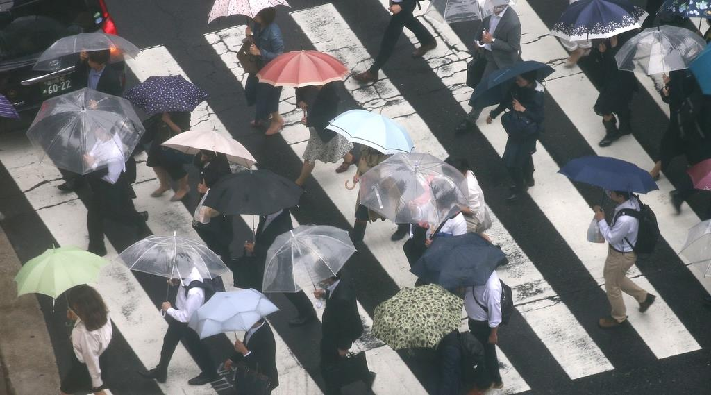 傘を差して足早に通勤するサラリーマンら=東京・大手町(鈴木健児撮影)