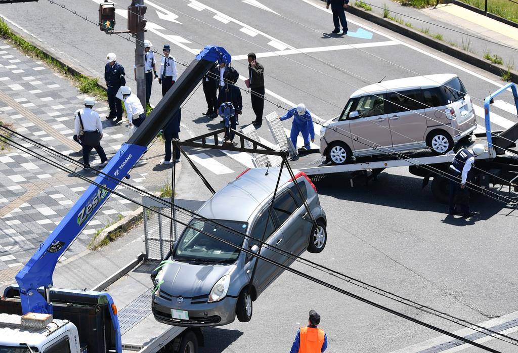 レッカーで運ばれる事故車両と、」事故現場を調べる警察官ら =5月8日午後、大津市(永田直也撮影)