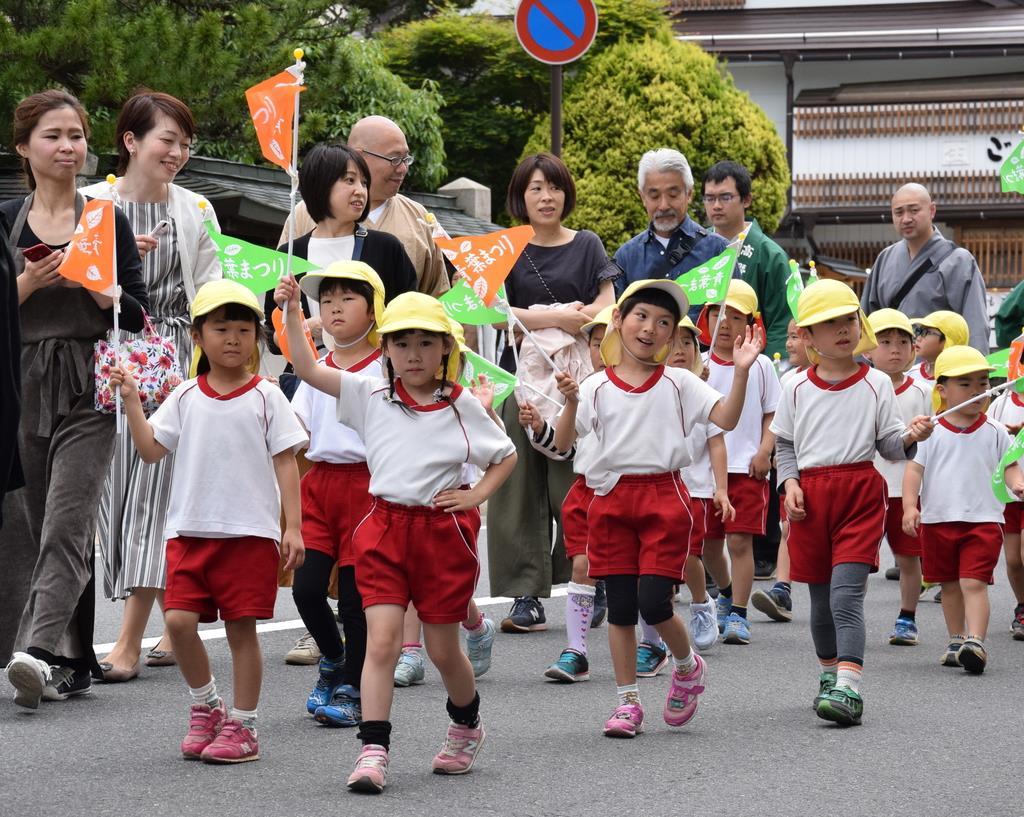 「青葉まつり」と記された旗を持って高野山の中心部を歩く園児ら=高野町(山田淳史撮影)