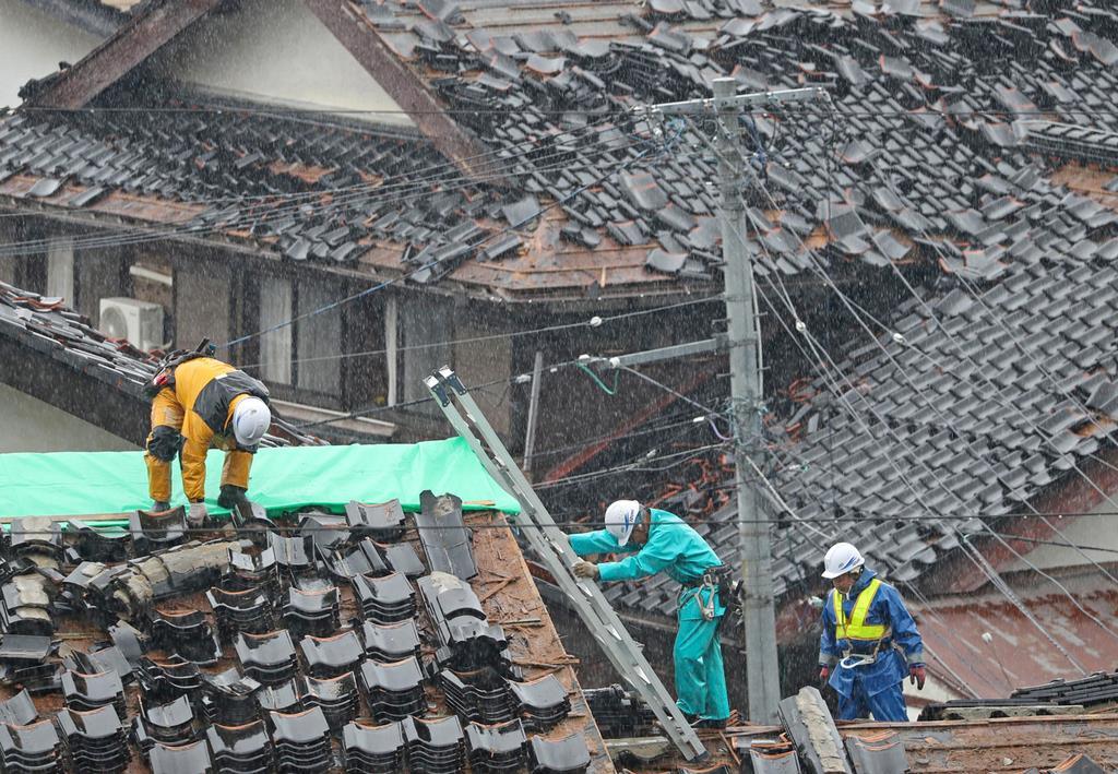 雨の中、瓦の落ちた屋根の養生をする作業員ら=19日午前、山形県鶴岡市小岩川地区(古厩正樹撮影)