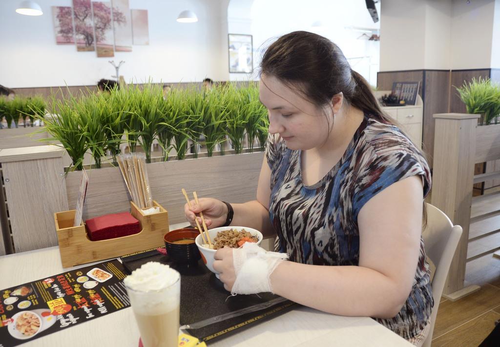 19日、モスクワで営業を開始した「松屋」で牛めしを食べる女性(共同)