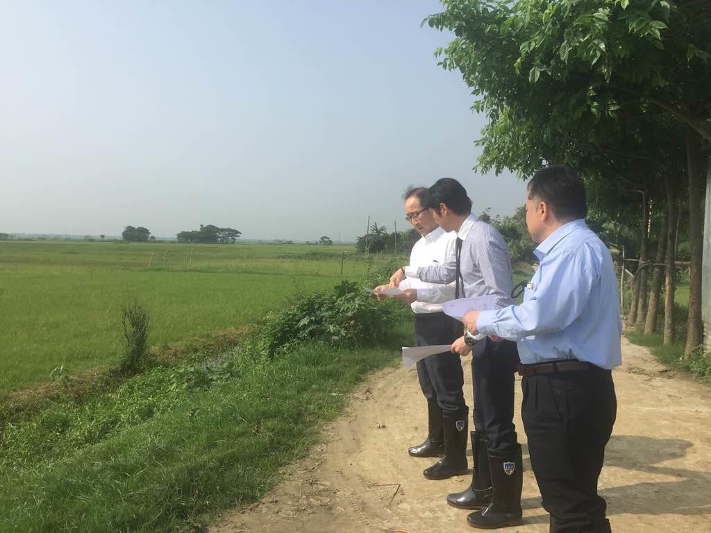 ダッカ近郊のSEZ開発用地を視察する住友商事の関係者(同社提供)