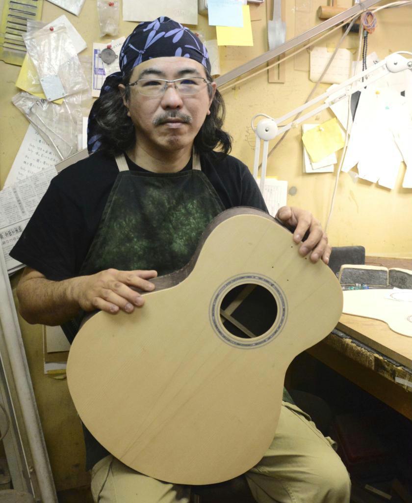 製作中のアコースティックギターを手にする合瀬潤一郎さん=佐賀市