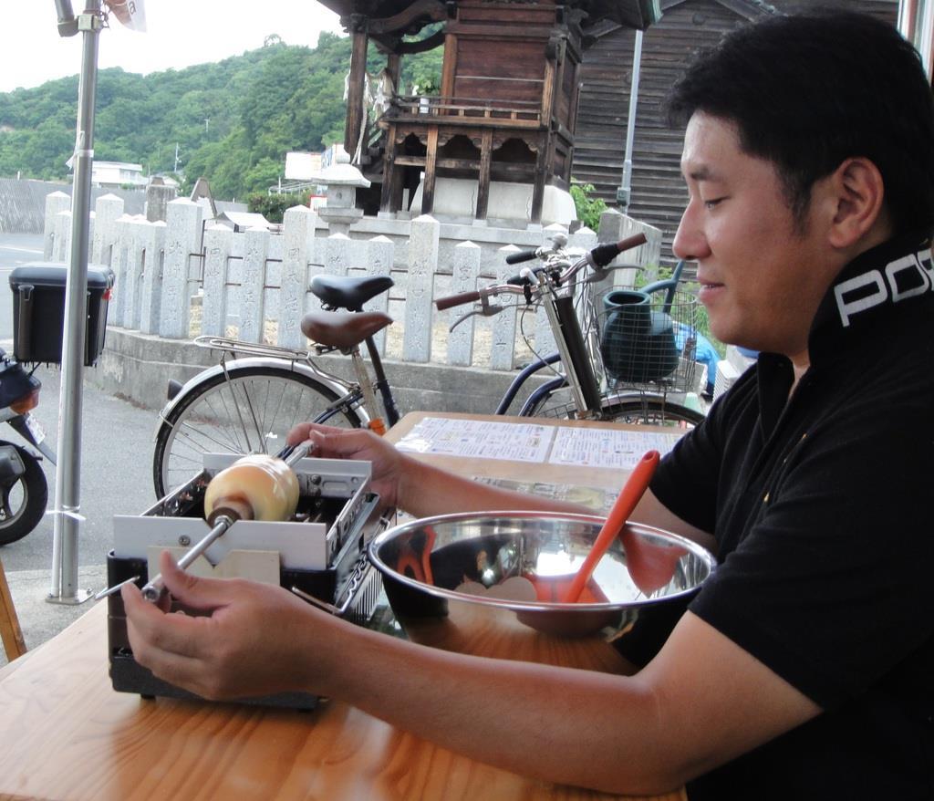 バウムクーヘンを焼く地域おこし協力隊小松健二さん=6月10日午後、広島市の似島