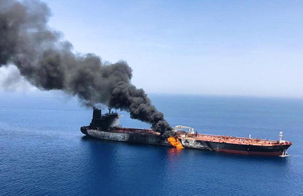 攻撃を受けて火災を起こし、オマーン湾で煙を上げるタンカー=13日、ホルムズ海峡付近(AP)