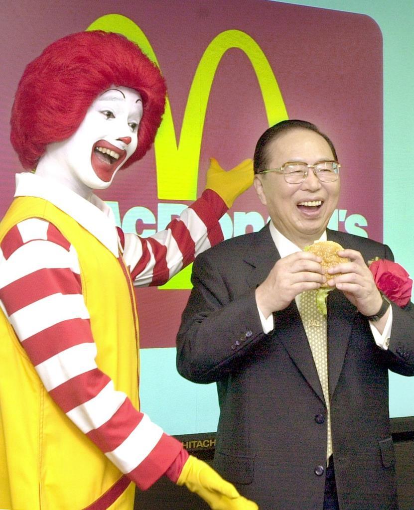 ハンバーガーを手に、会見で笑顔を見せる藤田田さん(右)=平成13年、東京都中央区