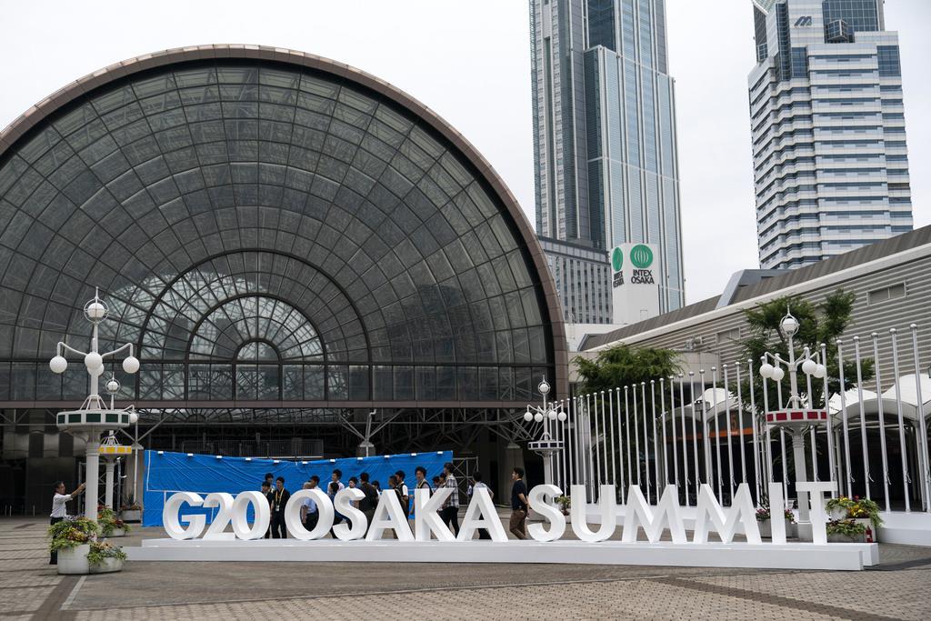 G20目前。ロゴ看板前で記念写真を撮影する人々もいた=26日、大阪(AP)