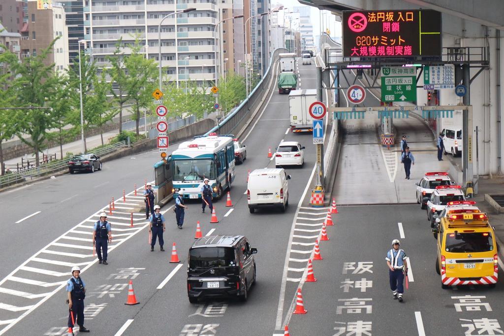 阪神高速・法円坂の入り口を封鎖する作業を行う警察官ら=27日午前6時7分、大阪市中央区