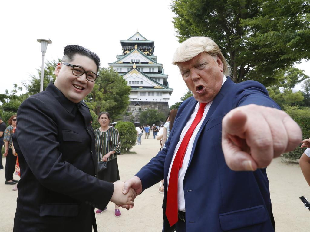 大阪城の前で握手を交わすトランプ米大統領(右)と北朝鮮の金正恩朝鮮労働党委員長のそっくりさん=26日午後、大阪市