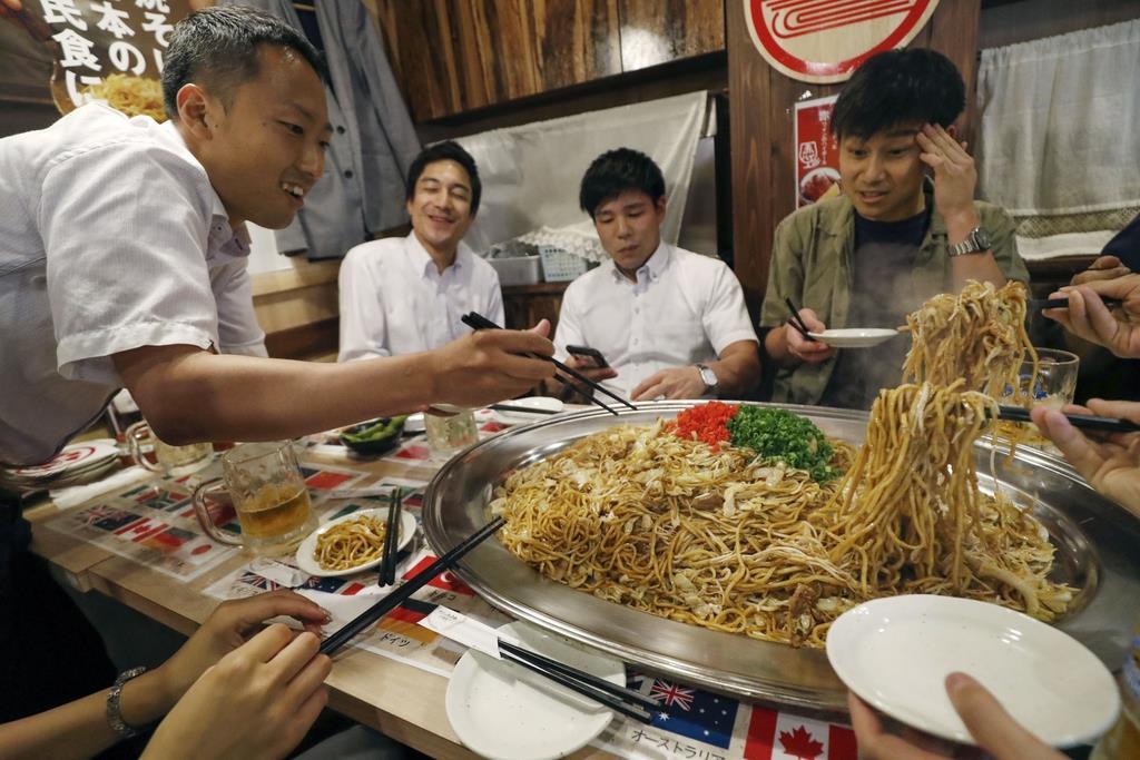 麺20玉を使った「G20焼きそば」に挑む男性客ら=兵庫県尼崎市