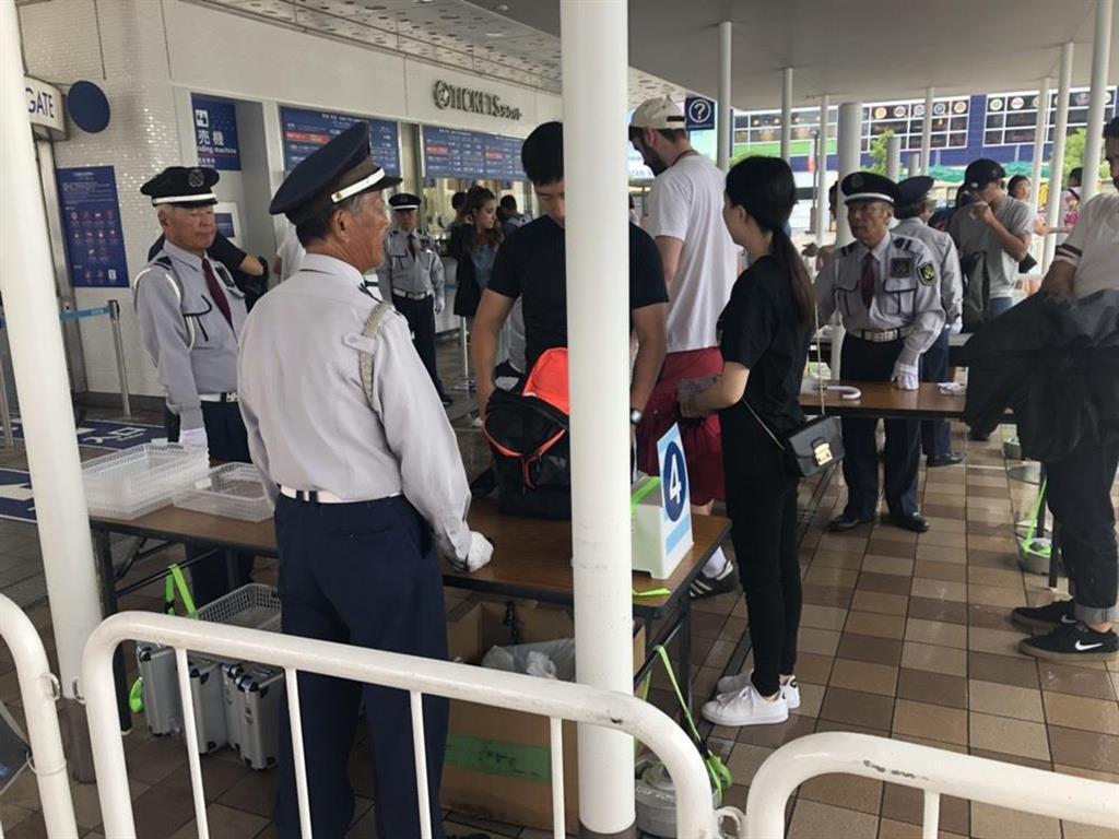 傘を手に手荷物検査を待つ観光客ら=27日午後、大阪市港区の海遊館(土屋宏剛撮影)