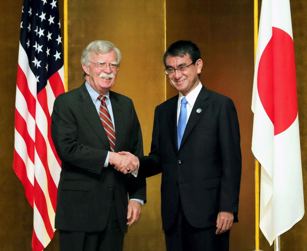 握手する米国のボルトン大統領補佐官(左)と河野外相=27日午後、大阪市内のホテル(代表撮影)