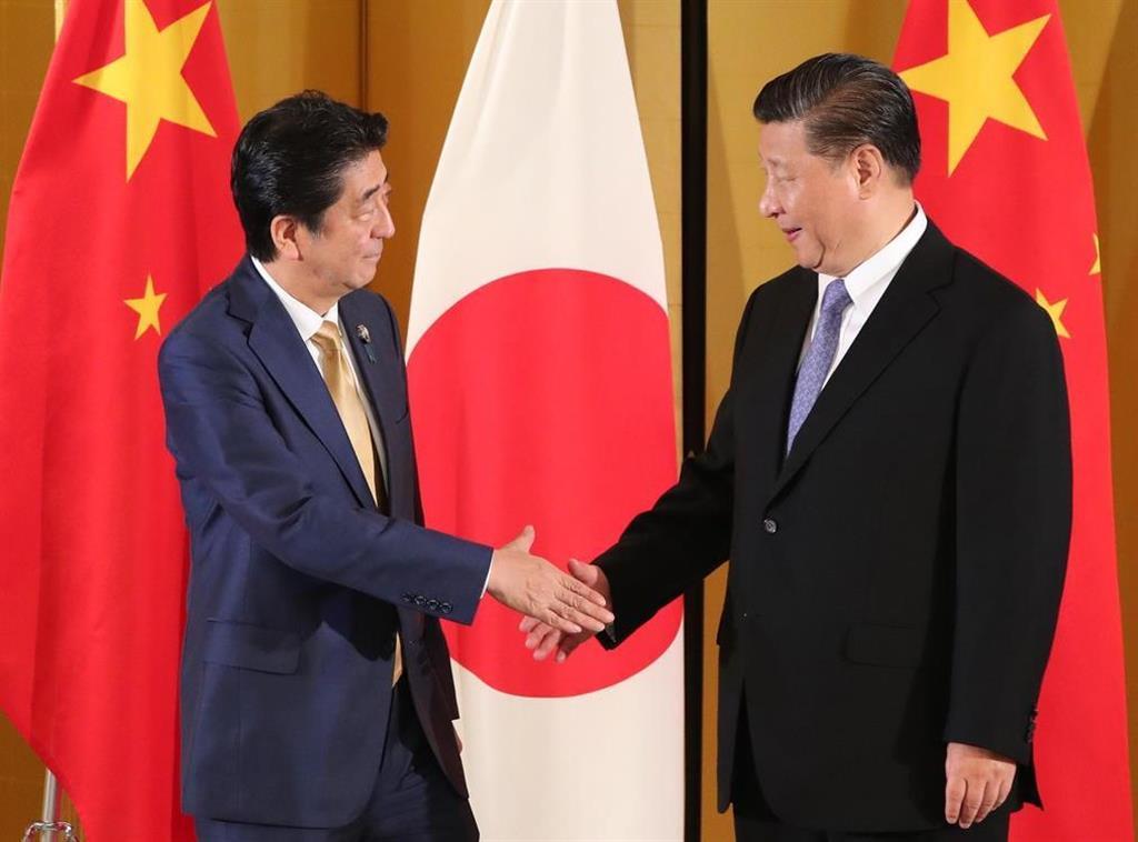 中国の習近平国家主席(右)と握手する安倍晋三首相=27日午後、大阪市北区(代表撮影)