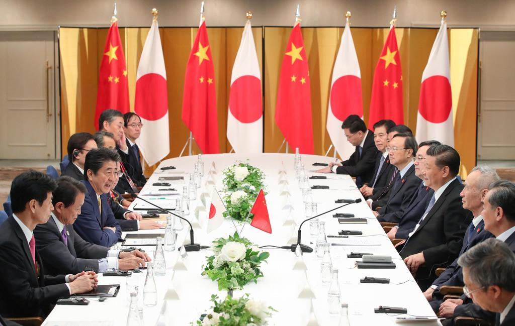 中国の習近平国家主席(右手前から4人目)と会談する安倍晋三首相(左手前から3人目)=27日午後、大阪市北区(代表撮影)