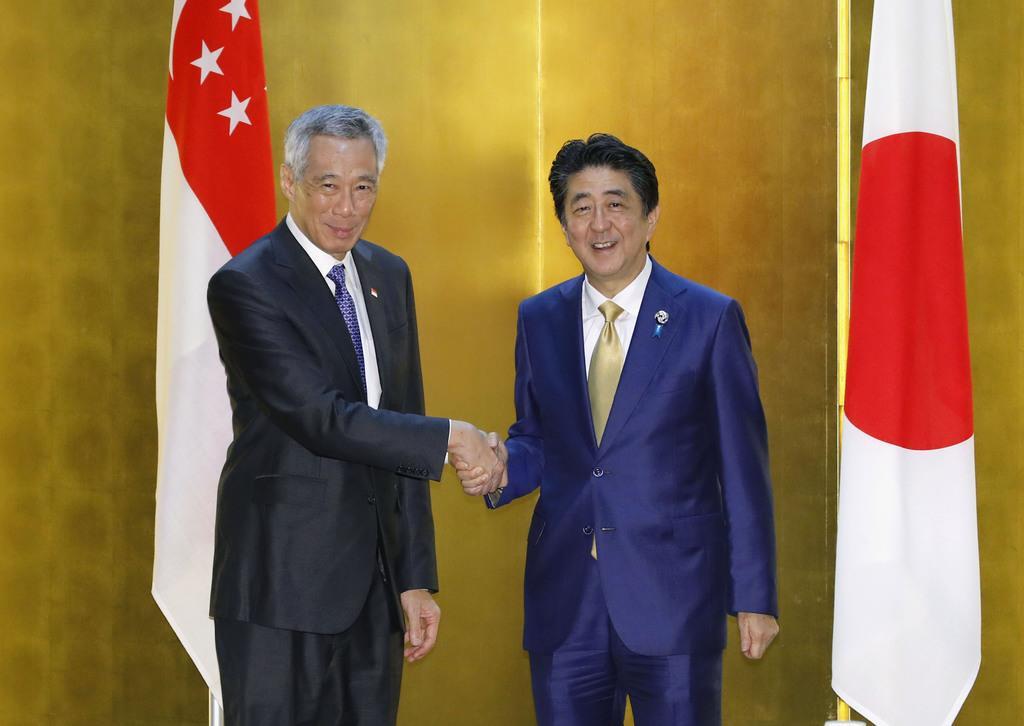 握手するシンガポールのリー・シェンロン首相(左)と安倍首相=27日午後、大阪市内のホテル