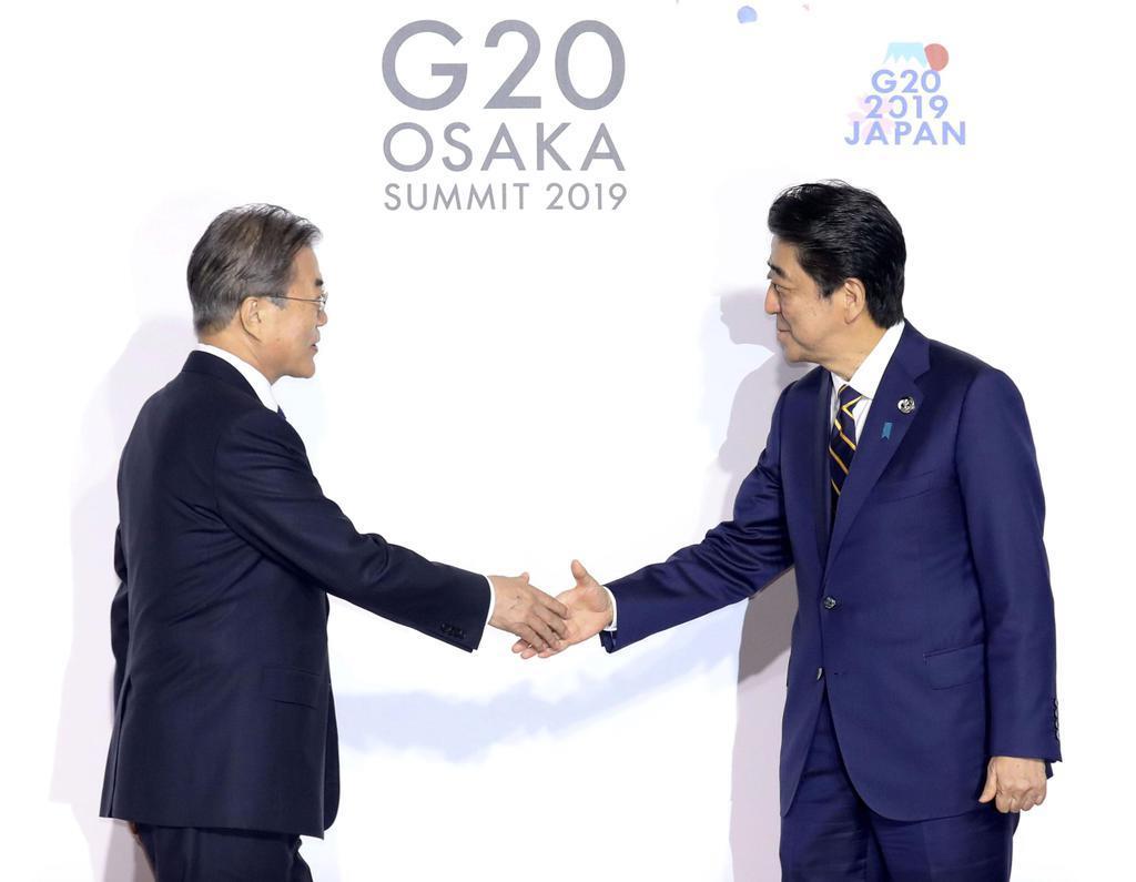 G20大阪サミットで韓国の文在寅大統領(左)を迎える安倍首相=28日午前、大阪市(代表撮影)