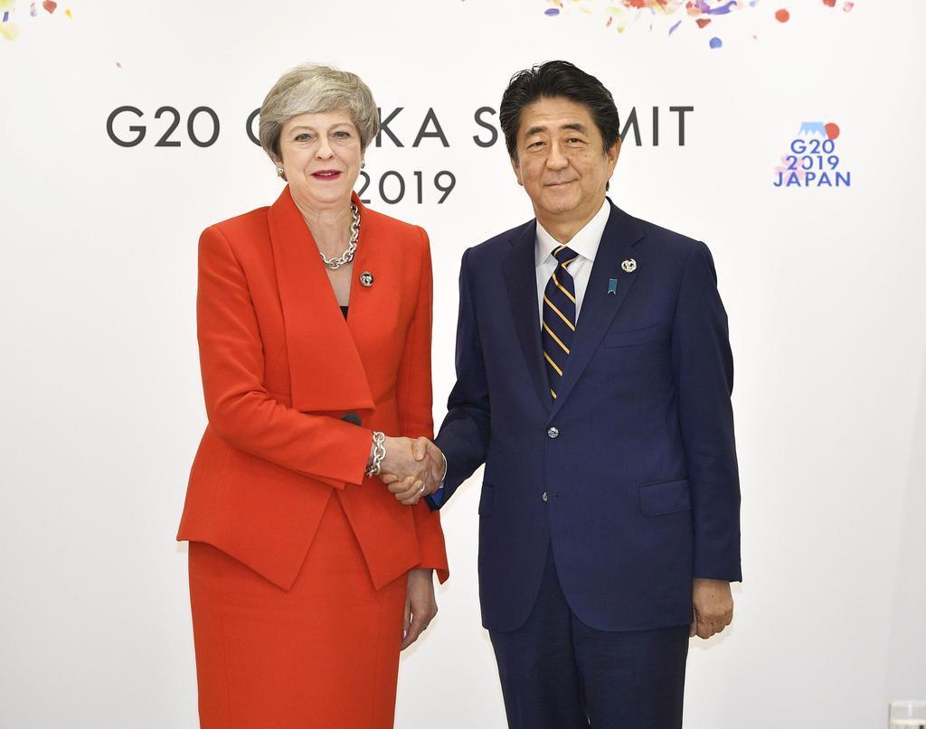 会談前に握手する英国のメイ首相(左)と安倍首相=28日午前、大阪市