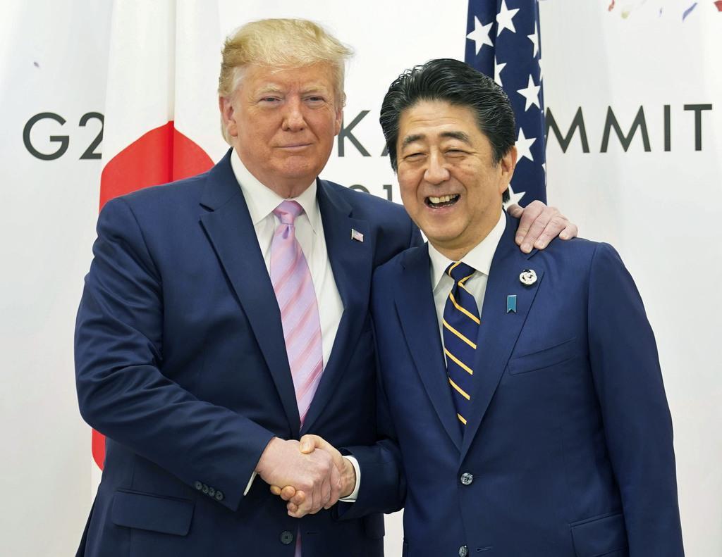 会談でトランプ米大統領(左)と握手する安倍首相=28日午前、大阪市(ロイター)