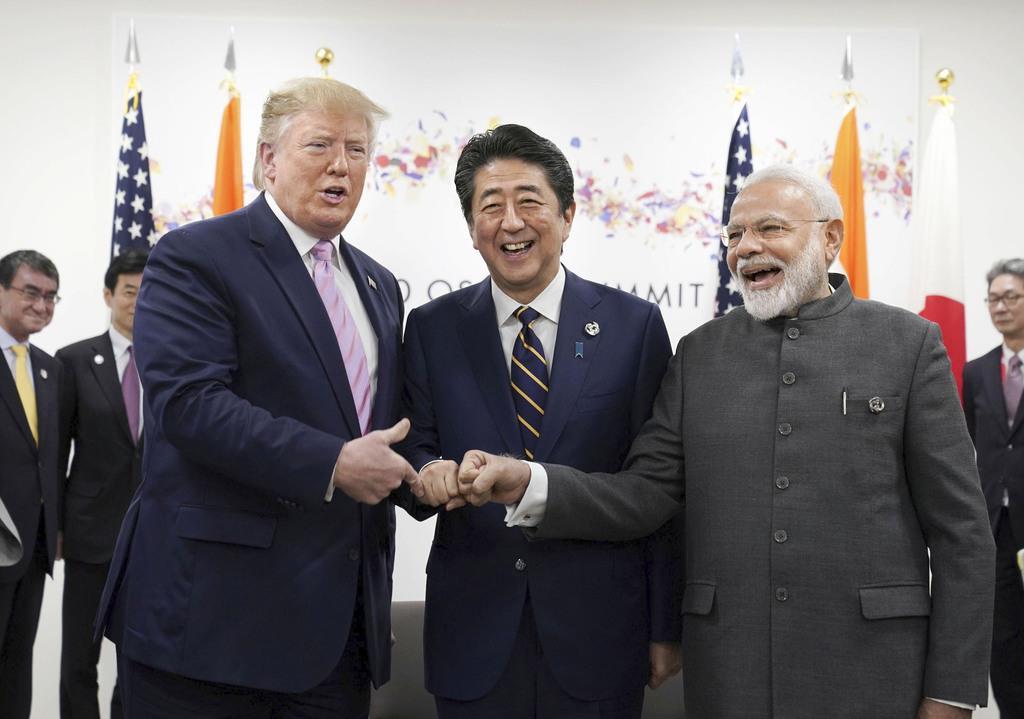 会談前にトランプ米大統領(左)、インドのモディ首相(右)と写真に納まる安倍首相=28日午後、大阪市(ロイター)