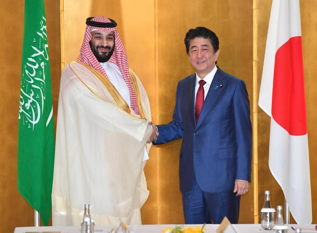 会談前、握手を交わすサウジアラビアのムハンマド皇太子(左)と安倍晋三首相=30日午前10時56分、大阪市内のホテル(代表撮影)