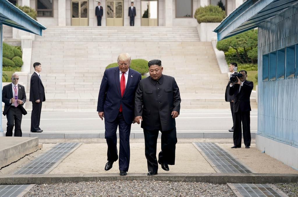 南北軍事境界線を越えて北朝鮮側から韓国側に入るトランプ米大統領(左)と北朝鮮の金正恩朝鮮労働党委員長=30日、板門店(ロイター)