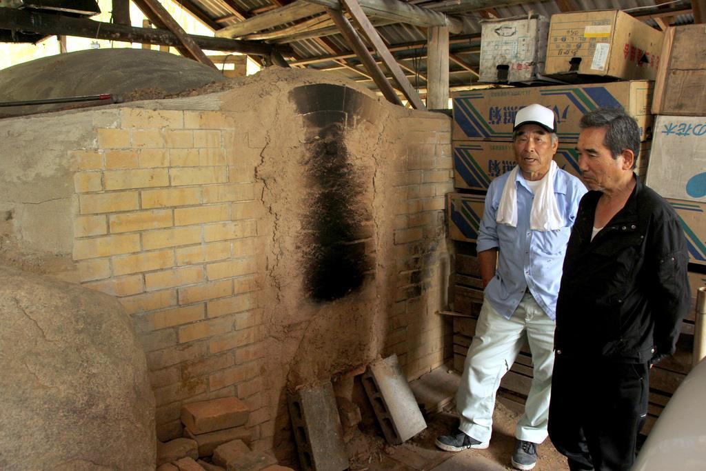 マービー釜で竹炭の生産に取り組む垣本嘉弘さん(左)=6月21日、岡山県倉敷市真備町(鈴木俊輔撮影)