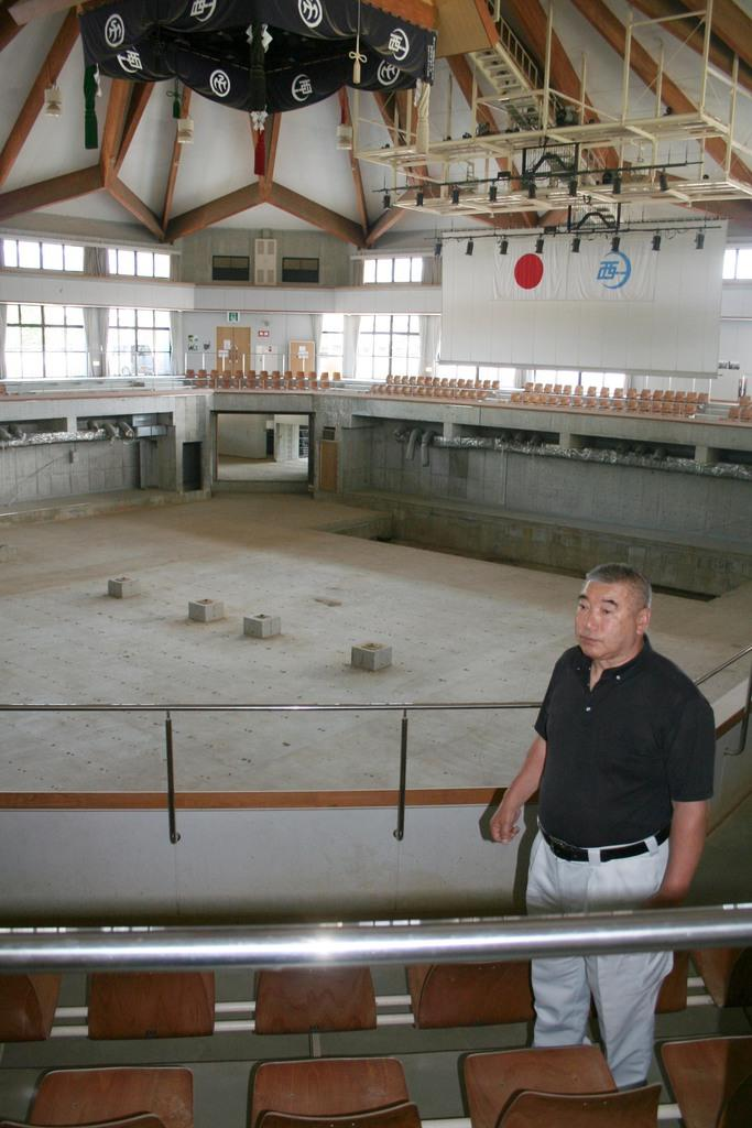 1階アリーナのコンクリートが露出した現状の乙亥会館。富本武夫館長が立つ2階の観客席の上まで水没した=愛媛県西予市野村町