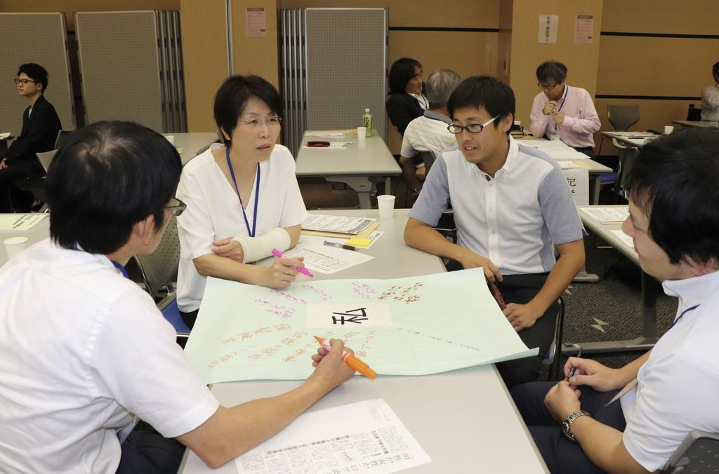 「NIE」の兵庫セミナーが神戸市で開かれ、模擬授業で意見交換する生徒役の教諭ら=5日午後