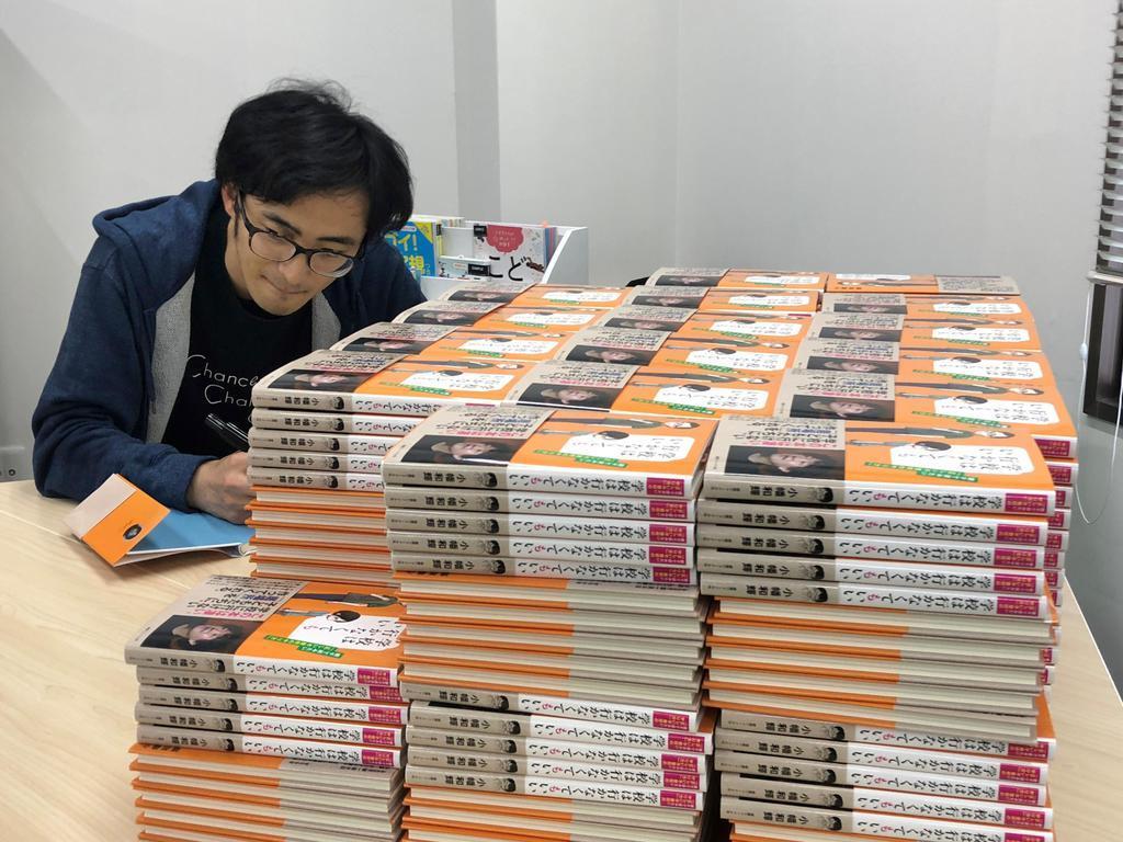 寄贈する著書にサインをする小幡和輝さん(本人提供)