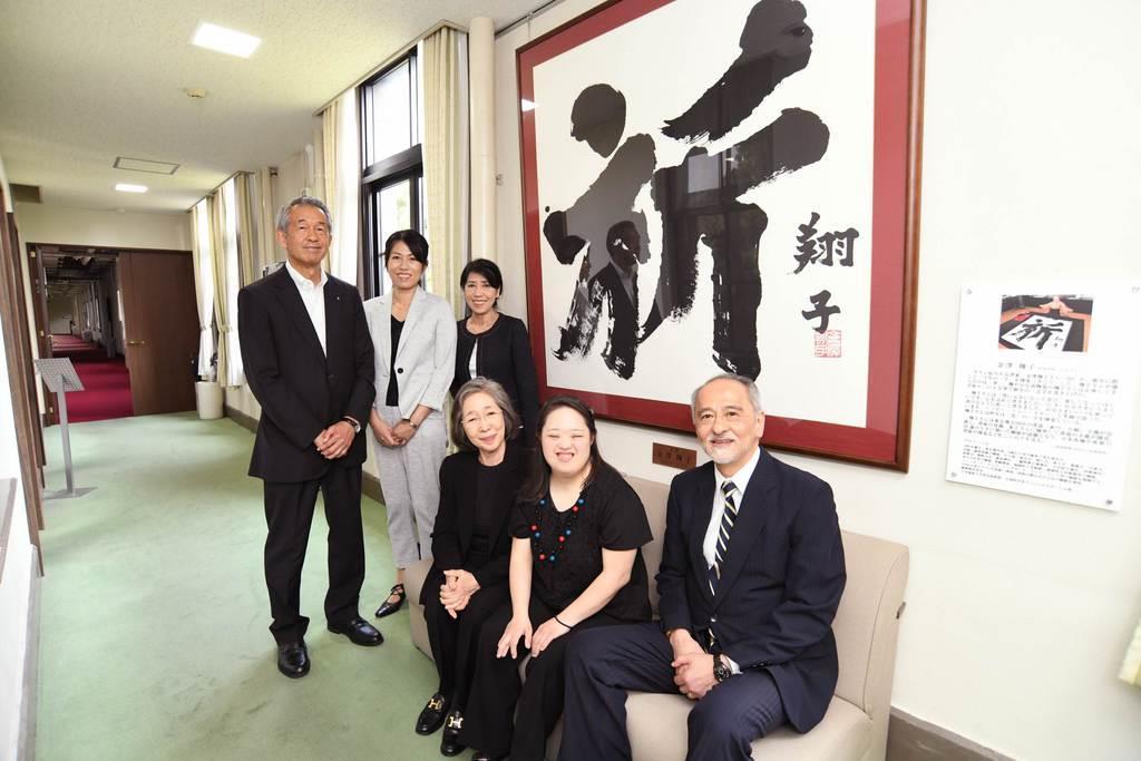 熊本大学に飾られた「祈」の前で記念撮影に収まる金澤翔子さん親子(中央手前)と大学関係者ら=8日、熊本市の熊本大学(同大提供)