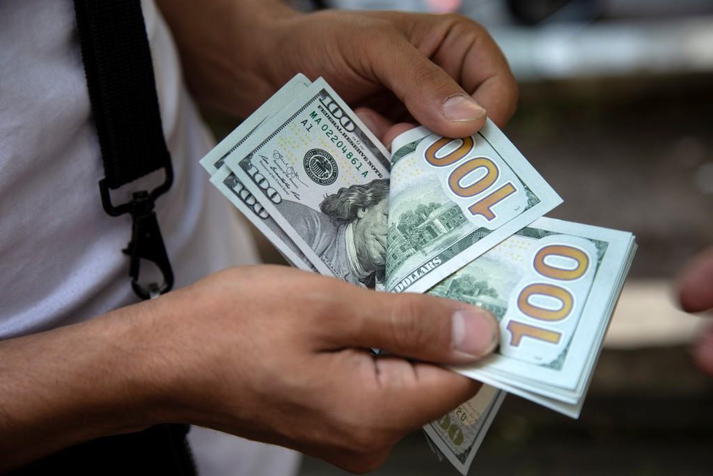 テヘランの街角で米ドルを数える人=7日(WANA・ロイター)