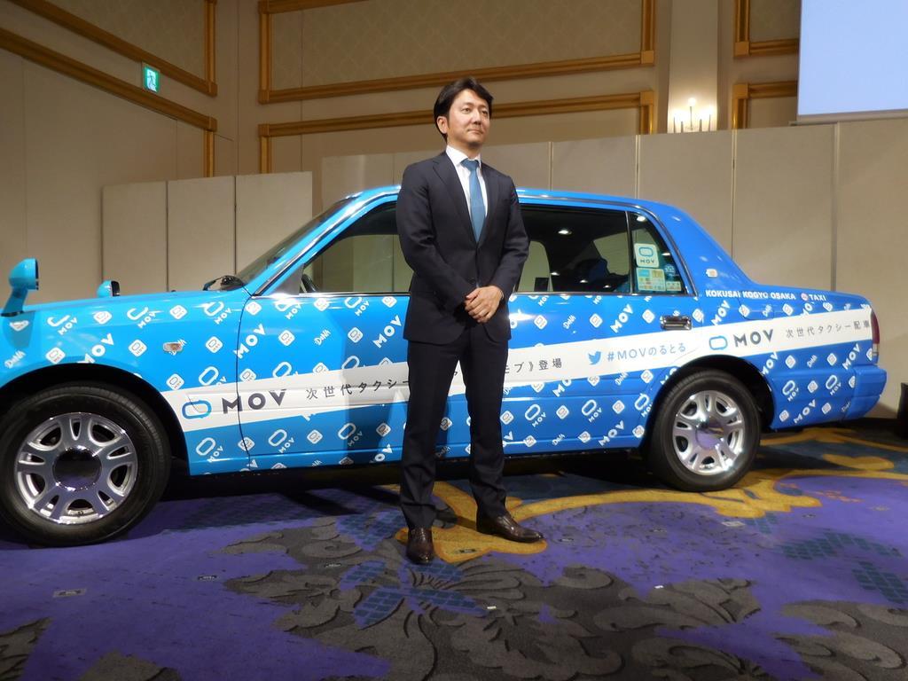 8日、大阪府、京都府での新タクシー配車サービス開始を発表したDeNAの中島宏常務執行役員と無料キャンペーン用タクシー=大阪市北区(黒川信雄撮影)