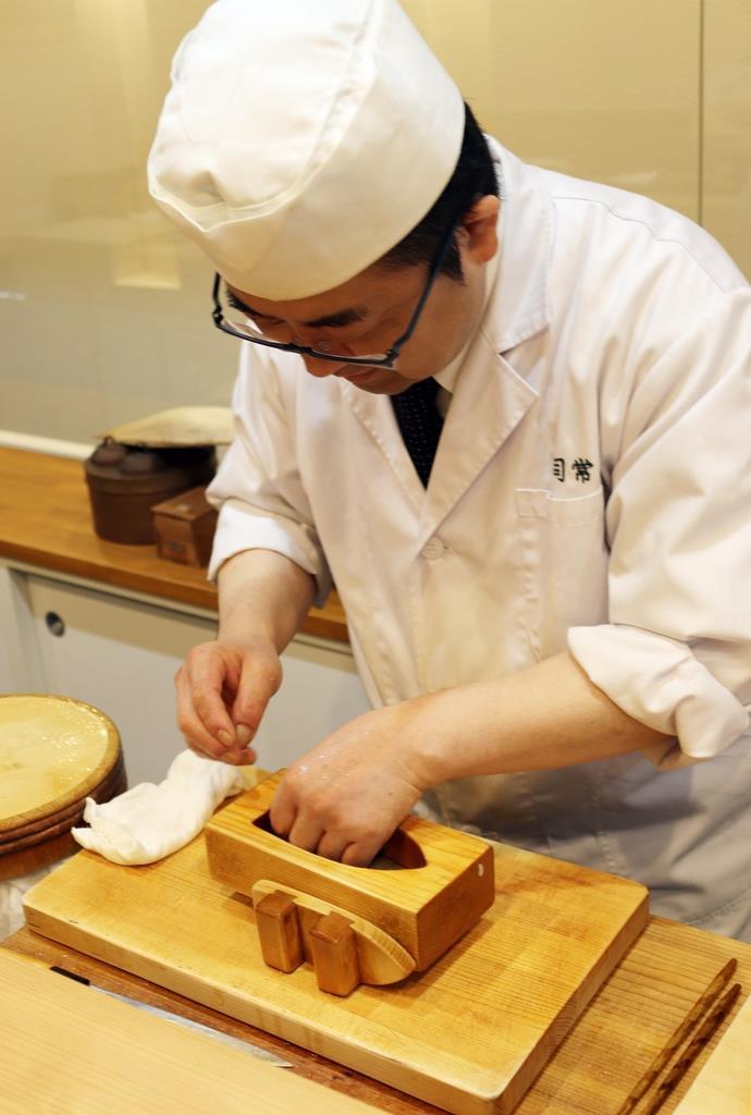 「発祥の店」ならではの舟形バッテラをつくる石川里留さん=大阪市北区の寿司常