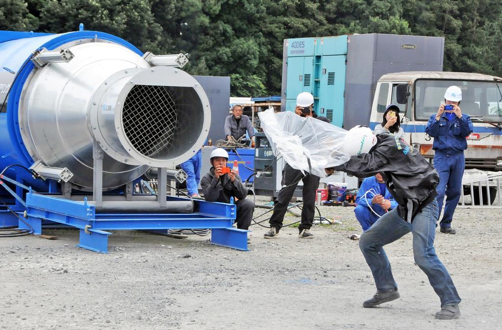 傘を差した状態で風速80メートルの暴風を体験する参加者=10日午前、茨城県筑西市花田(篠崎理撮影)