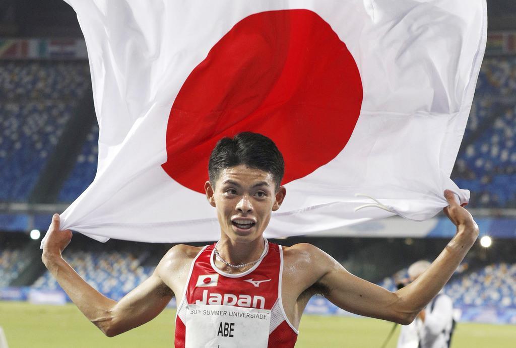 陸上男子1万メートルで2位となり、日の丸を掲げる阿部弘輝=ナポリ(共同)