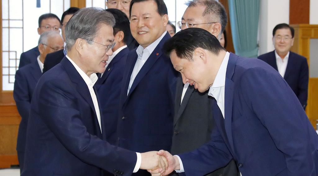 10日、財閥トップらとの会議に先立ち、SKグループの崔泰源会長(右)と握手する韓国の文在寅大統領=ソウル(聯合=共同)