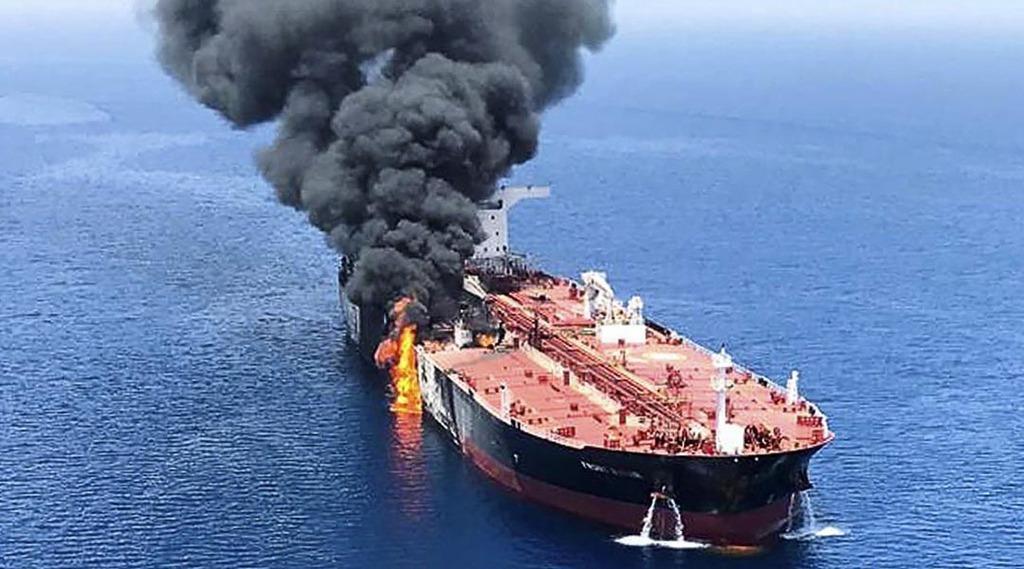 ホルムズ海峡付近で攻撃を受けて火災を起こし、オマーン湾で煙を上げるタンカー=6月(AP)