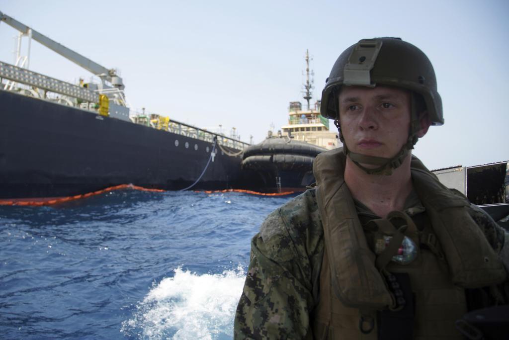 イラン沖で攻撃を受けた日本の海運会社が運航するタンカーと、米海軍兵=6月19日、アラブ首長国連邦(UAE)フジャイラ沖(AP)