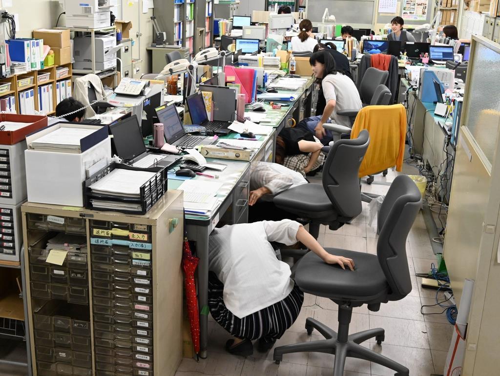 大地震を想定した「シェイクアウト訓練」で一斉に机の下にもぐる奈良市の職員ら=奈良市