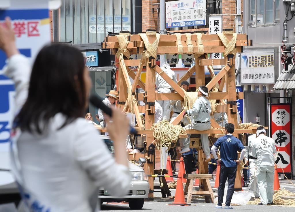 祇園祭の鉾が組み立てられる中、支持を訴える候補者 =10日午前、京都市下京区(永田直也撮影)